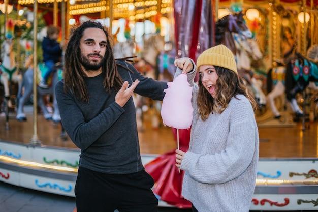 Молодая пара ест сладкую вату на рождественской ярмарке