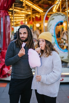 Young couple eating cotton candy at a christmas fair