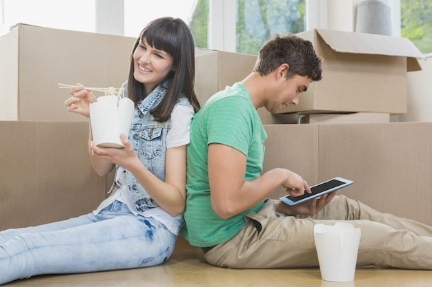 Young couple eating noodle and using digital tablet in their new house