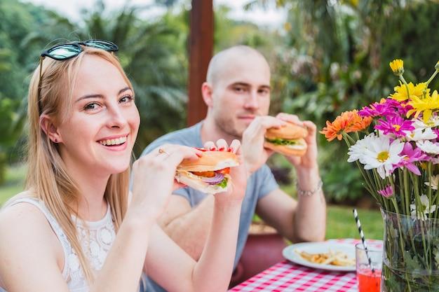 屋外で食べる若いカップル