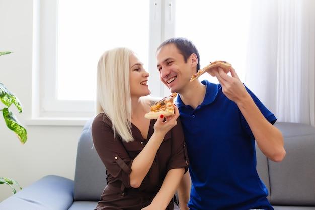 家でピザを食べる若いカップル