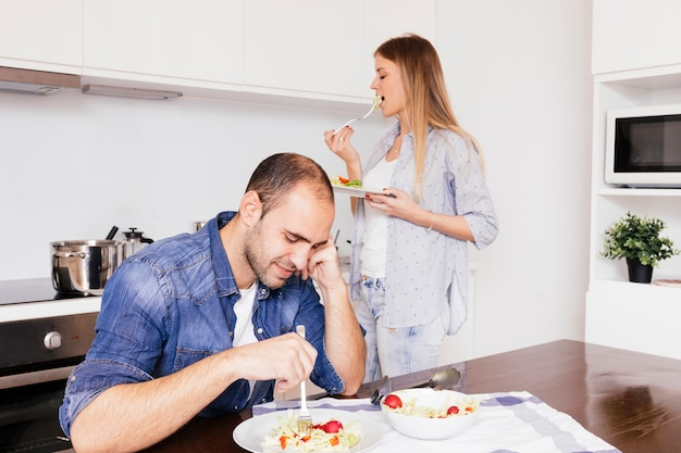 Young couple eating salad in the kitchen