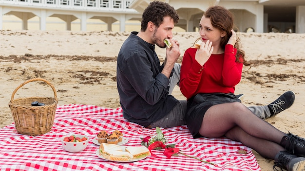 Young couple eating sandwiches on coverlet