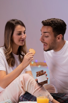 Young couple eating sweets in bed