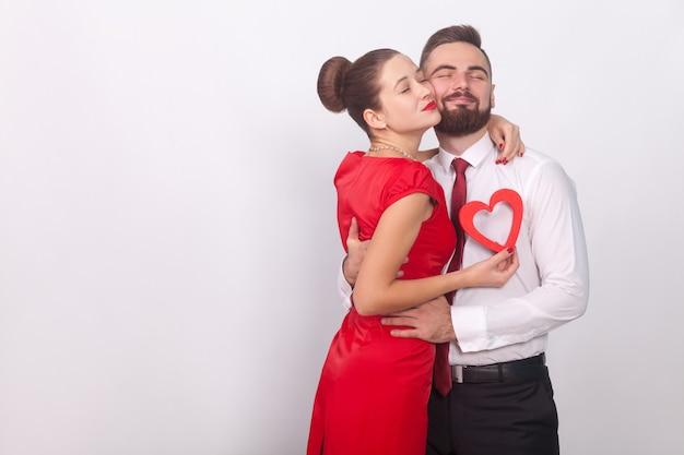 若いカップルは喜んで抱きしめ、目を閉じます。屋内、スタジオショット、灰色の背景で分離