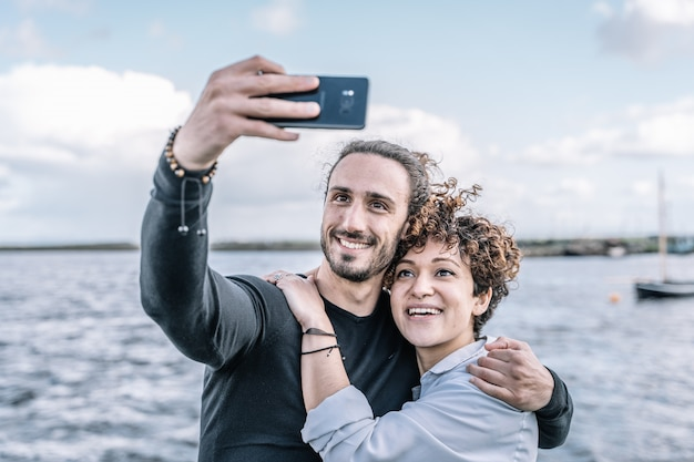 Young couple embraced by the shoulder making a selfie with the port and the sea out of focus