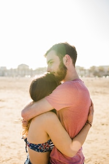 Young couple embracing each other on sandy beach on sunny day
