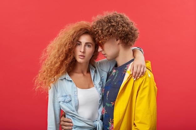 Giovani coppie che si abbracciano alla parete dello studio