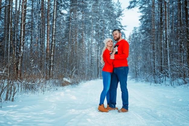 冬の森を受け入れる若いカップル。冬の休暇