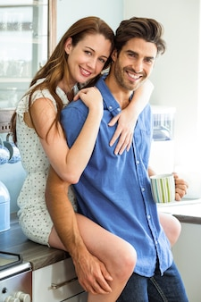 Young couple embracing in kitchen while having coffee