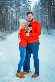 Young couple embracing in winter forest. winter vacations