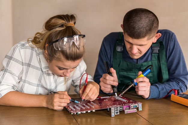 Young couple of engineers repairing computer device