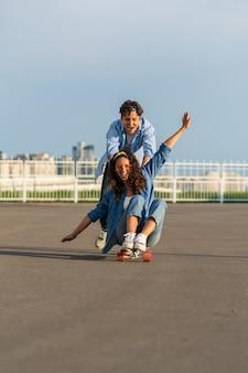 젊은 부부는 거리 힙스터 남자가 롱보드에 앉아 있는 여성의 등을 밀면서 스케이트보드를 함께 즐긴다