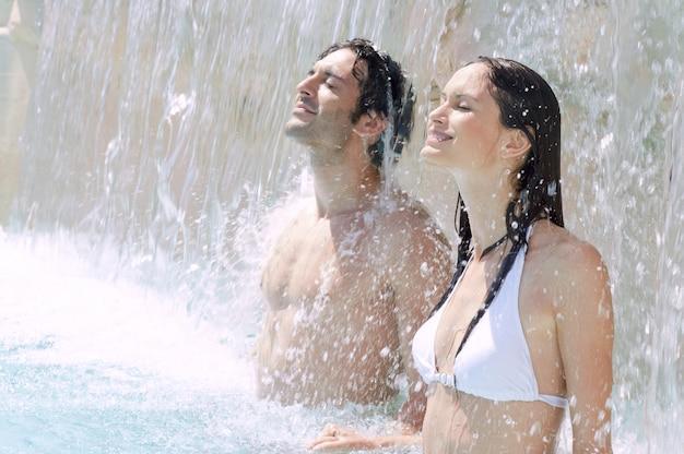 Молодая пара вместе наслаждается свежестью водопада в бассейне