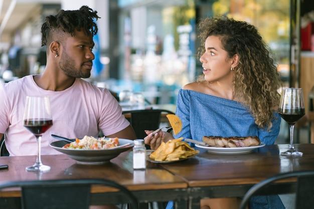 レストランでデートをしながら一緒に楽しんで楽しい時間を過ごす若いカップル。