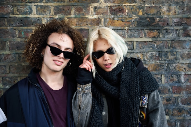Young couple enjoying camden town in front of a brick wall typical of london