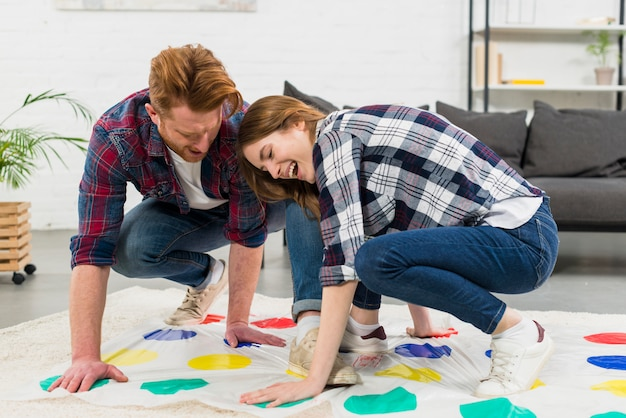 Young couple enjoying the color dot game on carpet at home