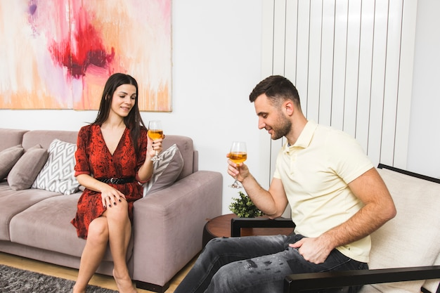 Young couple enjoying the drink sitting at home