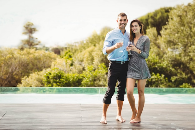 Young couple enjoying drinks near poolside at resort