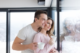 Young couple enjoying morning coffee by the window