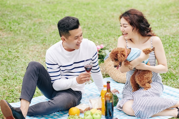 Young couple enjoying picninc in park, drinking wine and playing with dog