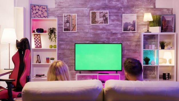 함께 소파에 앉아 온라인 게임을 즐기는 젊은 부부. 녹색 화면이 있는 tv.