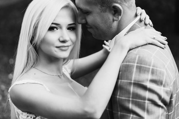 公園を散歩しながらロマンチックな瞬間を楽しむ若いカップル。スタイリッシュな新郎新婦のポーズと結婚式の日に公園でキスします。美しい白いドレスのエレガントな花嫁、スーツの新郎。