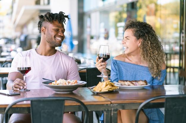 Giovani coppie che si divertono e trascorrono del tempo insieme mentre hanno un appuntamento in un ristorante.