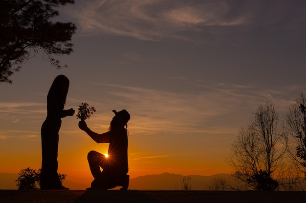 Young couple enjoying the sunset in the mountain