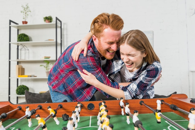 Young couple enjoying behind the table soccer game at home