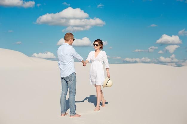 Молодая пара, наслаждаясь закатом в дюнах. романтический путешественник гуляет по пустыне. концепция приключенческого путешествия