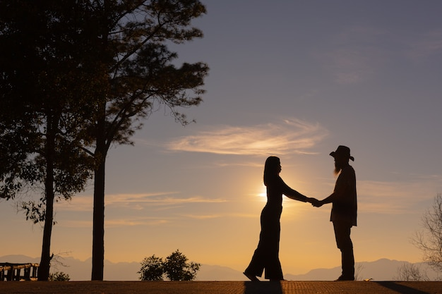 Молодая пара, наслаждаясь закатом в горах