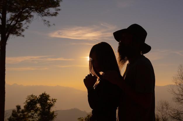 산에서 석양을 즐기는 젊은 부부