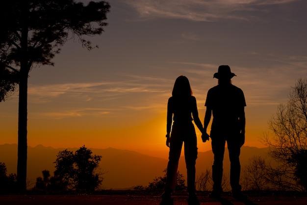山で夕日を楽しむ若いカップル