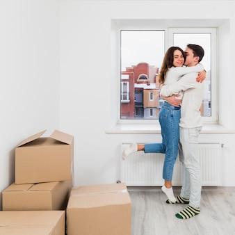 Young couple enjoying in their new home with cardboard boxes
