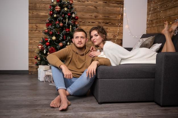 Молодая пара, наслаждаясь своим временем вместе дома. рождественская елка на фоне.