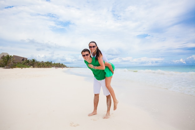 Young couple enjoying their vacation and have fun on a tropical beach