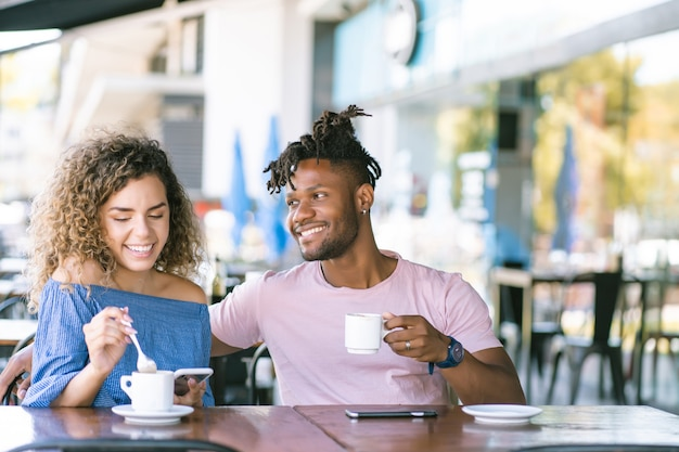 커피숍에서 커피 한 잔을 마시며 함께 즐기는 젊은 부부.
