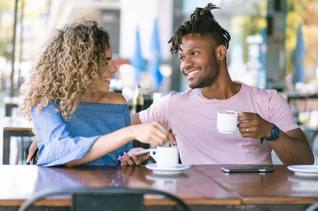 コーヒーショップで一杯のコーヒーを飲みながら一緒に楽しんでいる若いカップル。