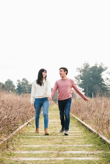 Young couple enjoying walk along tracks