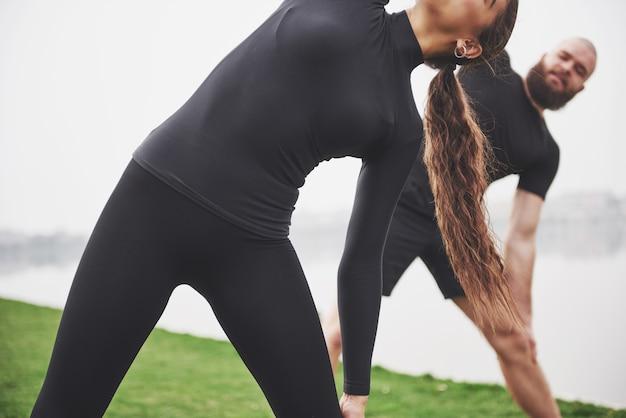 Una giovane coppia si diverte a fare sport al mattino all'aperto. riscaldati prima dell'esercizio