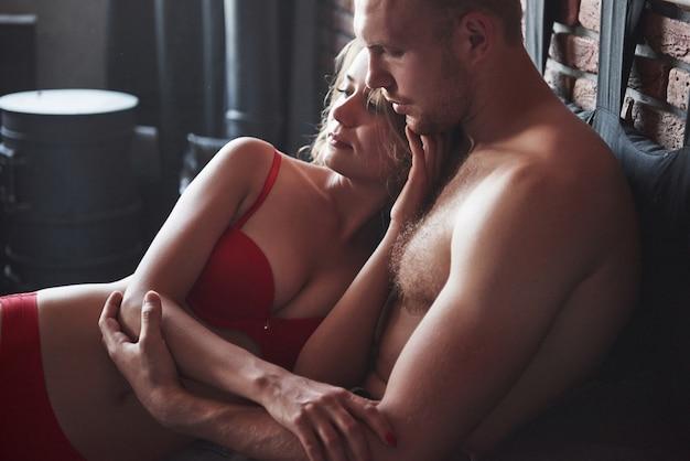 Una giovane coppia si diverte a dormire, sdraiati a letto insieme durante il giorno.
