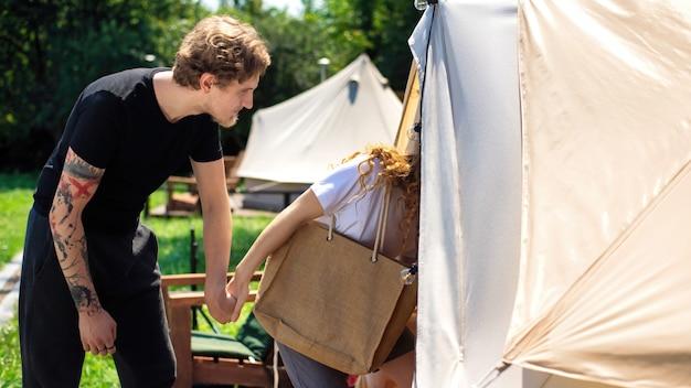 手をつないでグランピングでテントに入る若いカップル。周りの緑
