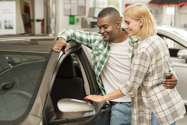 Young couple examining new car at the dealership
