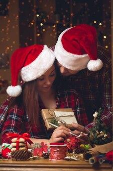 若いカップルがクリスマスプレゼントを交換します。