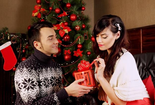 Молодая пара обменивается подарками на рождество