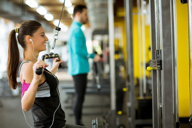 Young couple exercise bodybuilding exercises in the modern gym