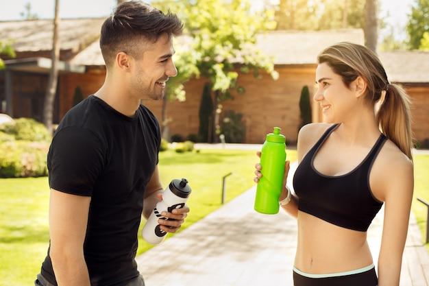 若いカップルは屋外で健康的なライフスタイルを一緒に運動します