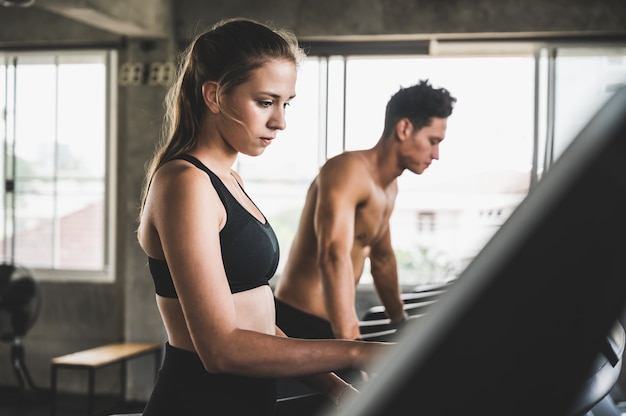 Young couple exercising by running on the treadmill to maintain good health always