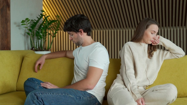 Young couple experiencing relationship problems is sitting next to each other at home on a yellow sofa